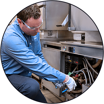 picture of repairman fixing commercial kitchen appliance
