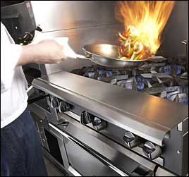 image of restaurant chef cooking over commercial gas range