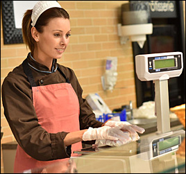 image of restaurant or deli clerk using food pricing scale at checkout counter